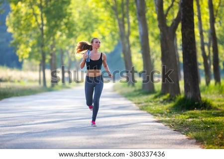 Jogging woman with a bottle of water - stock photo