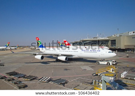 JOHANNESBURG - APRIL 18:Airbus A340 disembarking passengers after intercontinental flights on April 18, 2012 in Johannesburg, South Africa. Johannesburg Tambo airport is the busiest airport in Africa - stock photo
