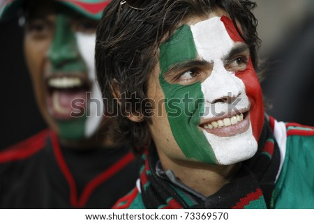 JOHANNESBURG, SOUTH AFRICA - JUNE 27:  Mexico supporters smiling and cheering at a World Cup soccer match between Argentina and Mexico June 27, 2010 in Johannesburg, South Africa. - stock photo