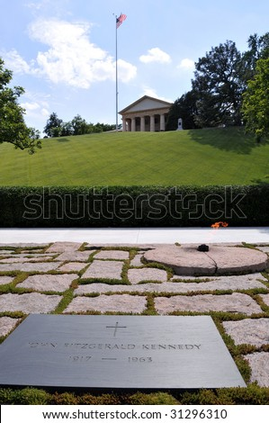 John F. Kennedy's grave, the eternal flame, and Arlington House in the background, at the Arlington National Cemetery in Arlington, Virginia, near Washington DC - stock photo