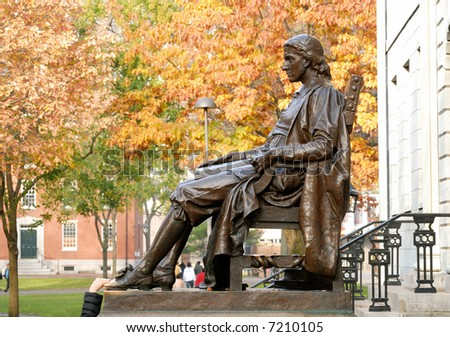 John Harvard statue. Tourist's hand rubbing his shoe for luck.
