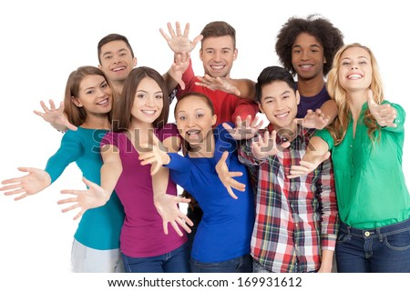 Join us! Group of cheerful young multi-ethnic people standing close to each other and gesturing while standing isolated on white