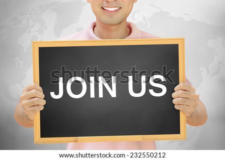 JOIN US sign on blackboard held by smiling man - stock photo