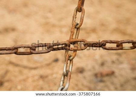 Joined old rusty chain in cross, close up view of poor chain and screw - stock photo