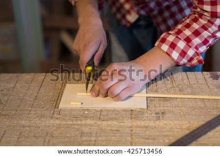 joiner cutter cuts a wooden stick made of wood toys, woodworking shop, the concept of a hobby, handmade