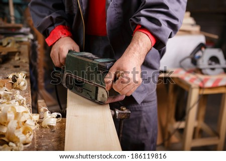 Joiner with a belt sander on a wooden board with sawdust - stock photo