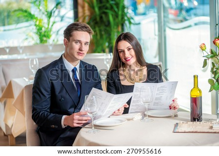 Joint selection of dishes on the anniversary. Romantic dinner in the restaurant. Young loving couple while visiting a restaurant menu holds in his hands and with a smile looking at the camera - stock photo