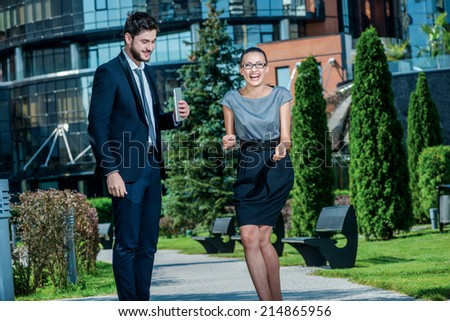 Jokes at work. Smiling businessman and successful businesswoman in formal clothes standing on the street and discuss business matters. Young businesspeople laughing at the camera