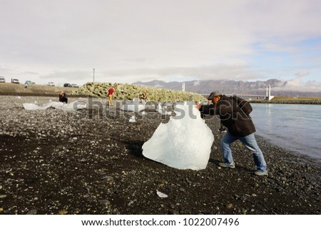 Jokulsarlon,Iceland - September 2017: a tourist try to move the big broken glacier, the ice at the mouth of the great glacial lake of Jokulsarlon: Diamond Beach.southeast Iceland