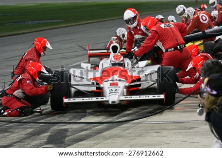 Joliet Illinois, USA - August 29, 2009: IndyCar Racing League. Pit stop. Ryan Brisco driver, Penske racing team. Team changes tires and fuels the car. Chicagoland speedway. Night Racing under lights. - stock photo