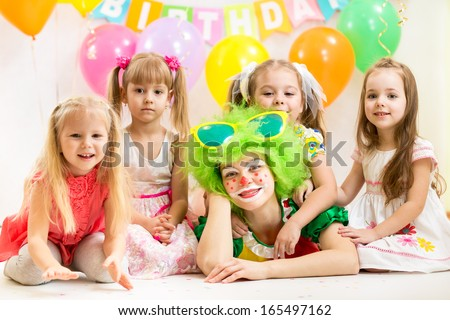jolly children and clown on birthday party - stock photo
