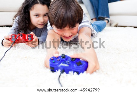 Jolly children playing video games lying on the floor with their parents in the background - stock photo