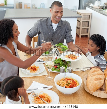 Jolly family dining together in the kitchen - stock photo