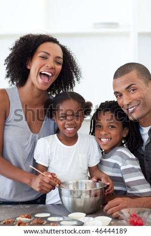 Jolly family making cookies together in the kitchen - stock photo