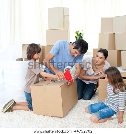 Jolly Family moving house packing boxes - stock photo