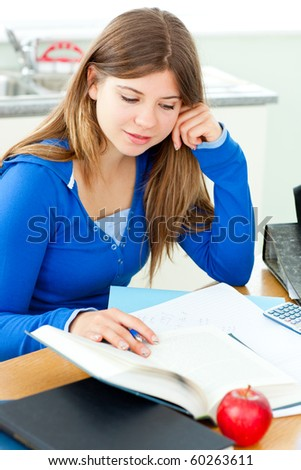 Jolly female teenager studying in the kitchen at home