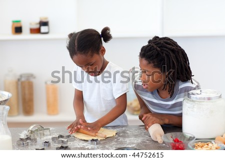 Jolly siblings cooking biscuits in the kitchen - stock photo