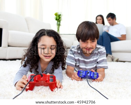 Jolly siblings playing video games lying on the floor with their parents in the background - stock photo