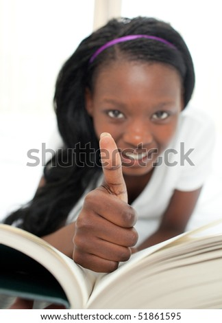 Jolly woman reading a book with thumb up - stock photo