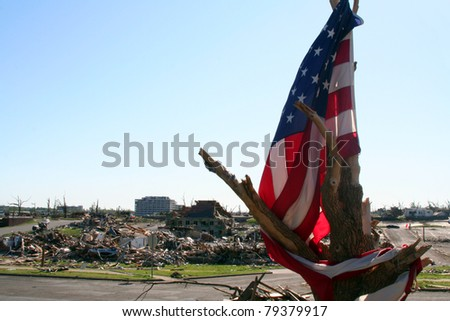 JOPLIN, MISSOURI-MAY 22:  American flag in a stripped tree with the city and St. John's hospital that was destroyed in the EF5 Tornado on May 22, 2011 in Joplin - stock photo