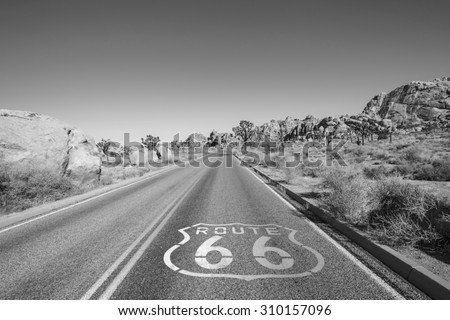 Joshua Tree highway with Route 66 pavement sign in black and white. - stock photo