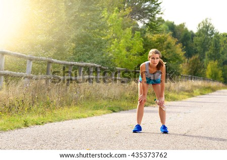 Joung woman taking a rest while jogging outdoors