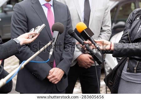 Journalists making interview with businessperson or politician - stock photo