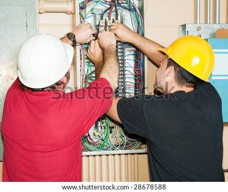 Journeyman and apprentice electrician working to repair a circuit breaker panel. - stock photo