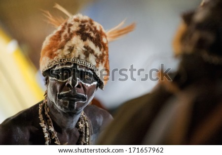 JOW VILLAGE, ASMAT DISTRICT,  NEW GUINEA, INDONESIA - JUNE 28: Headhunter of a tribe of Asmat shows traditional and national dresses. June 28, 2012, Jow Village, Asmat, Irian Jaya province, Indonesia  - stock photo