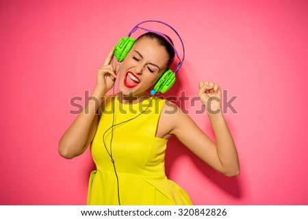 Joy and music. Colorful studio portrait of happy young brunette woman with earphones is dancing and singing. - stock photo