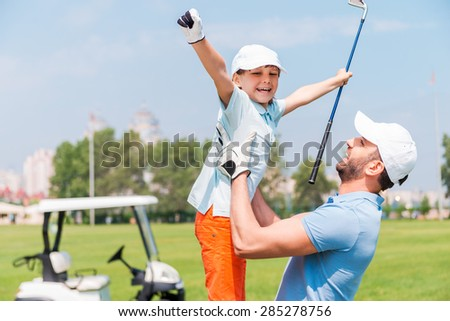 Joy of great game. Excited young man picking up his son while standing on the golf course - stock photo