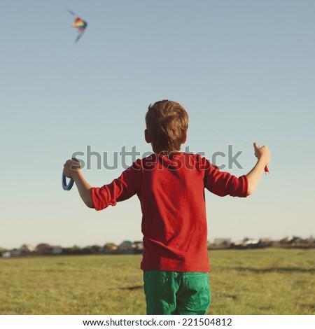 joy teen flies kite into blue sky, outdoor, summer - stock photo