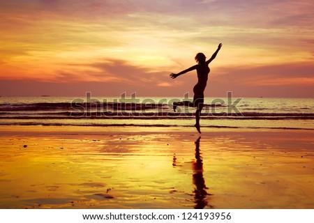 joy, woman jumping on the beach at sunset - stock photo