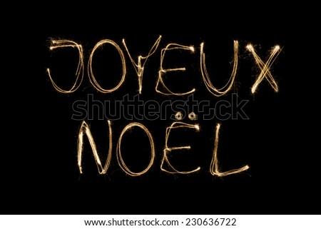 Joyeux Noel (French Merry Christmas) written with a sparkler isolated on black background - stock photo