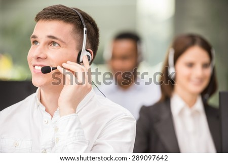 Joyful agent working in a call centre with his headset. - stock photo