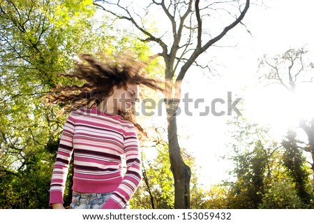 Joyful and energetic young teenager girl flicking her hair around in the air while visiting an autumn forest park with yellow tree leaves during a sunny fall season day. - stock photo