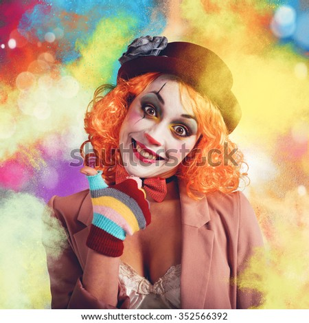 Joyful and smiling clown between multi-colour powders