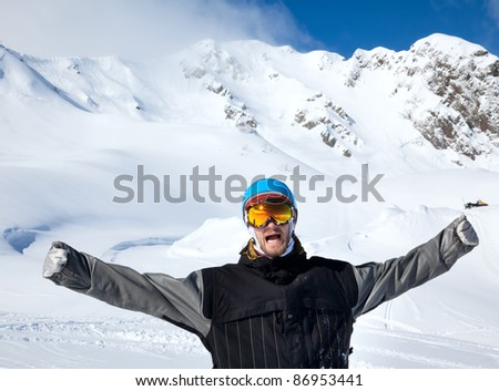 Joyful athlete Snowboarder on the background beautiful Caucasus mountains and blue sky - stock photo