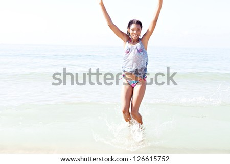"Joyful attractive ""african american"" woman jumping on the shore while on vacation, having fun on the beach. - stock photo"
