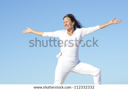 Joyful attractive senior woman being happy and active, isolated with blue sky as background and copy space - stock photo