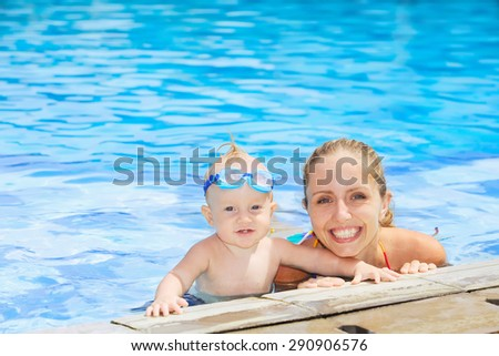 Joyful baby boy in underwater goggles swimming with fun with happy mother in outdoor pool. Active lifestyle, water sports activity and exercising with parents on summer family vacation with child - stock photo