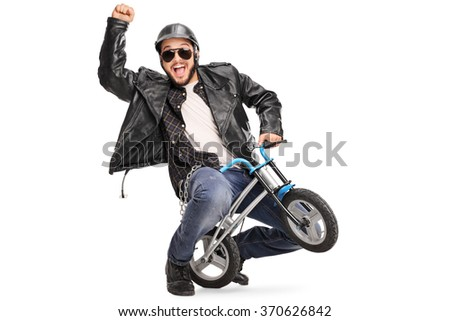 Joyful biker riding a small childish bicycle and gesturing with his hand isolated on white background - stock photo