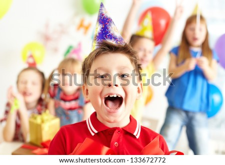 Joyful boy looking at camera with his friends on background - stock photo