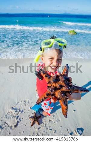 Joyful boy on the tropical beach with equipment to scuba diving and starfish. Focus on the starfish. - stock photo