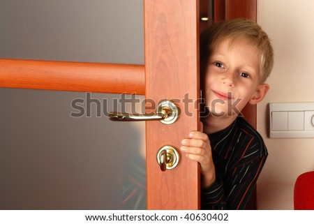 Joyful boy peeping out from behind door - stock photo