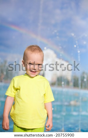 Joyful boy under fountain water jets and rainbow - stock photo