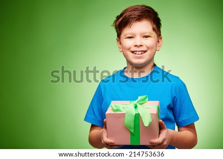 Joyful boy with giftbox looking at camera in isolation - stock photo