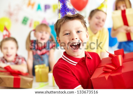 Joyful boy with giftbox looking at camera with his friends on background - stock photo