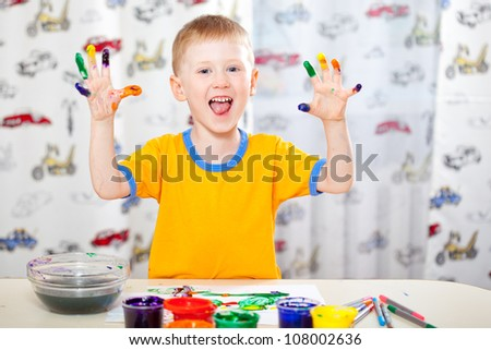 joyful boy with painted fingers, painting at home