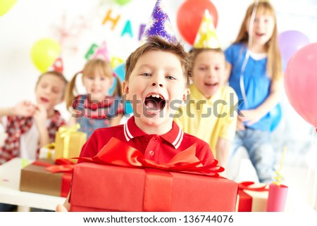 Joyful boy with present looking at camera with his friends on background